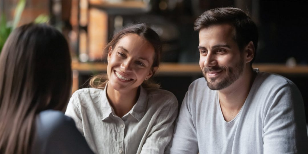 Image of a young couple discussing their first mortgage